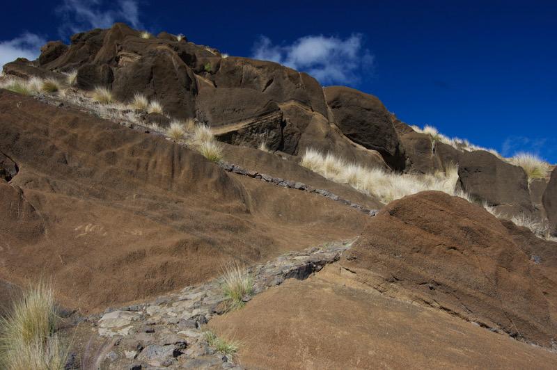 Vulkanische Schichten neben dem Stein gepflasterten Wanderweg oberhalb von San Pedro