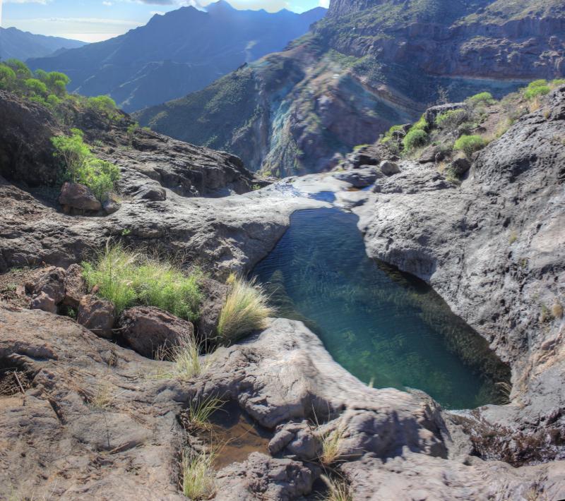 Wasserloch in einem Bachgrund und Blick auf die farbigen Azulejos Felsen