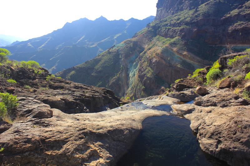 Wasserloch beim Abstieg der Azulejos Wanderung. Im Hintergrund, Mitte rechts, die bunten Felsen von Los Azulejos
