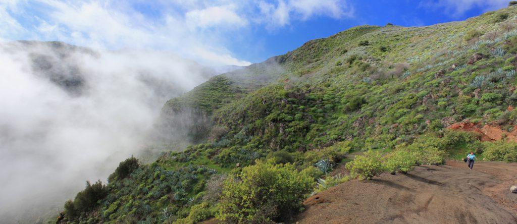 Wolken über der Falkenschlucht. Breite Fahrstrasse und Wanderer auf dem Weg nach oben.