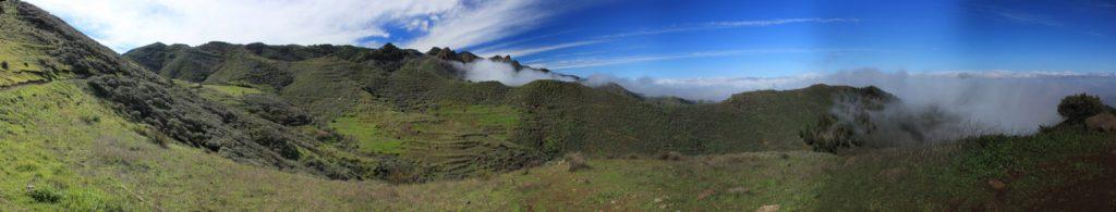 Grüne Wiesen und Terrassenfelder mit Passatwolken auf der Nordostseite der Insel Gran Canaria